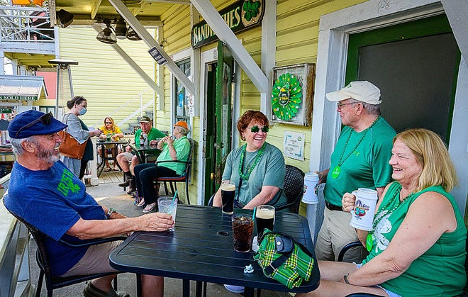 Friends John and Judy Haley and Don and Peg Scully enjoy drinks to celebrate St. Partick's Day on the front porch of Ann O'Malley's in St. Augustine on Wednesday, March 17, 2021.