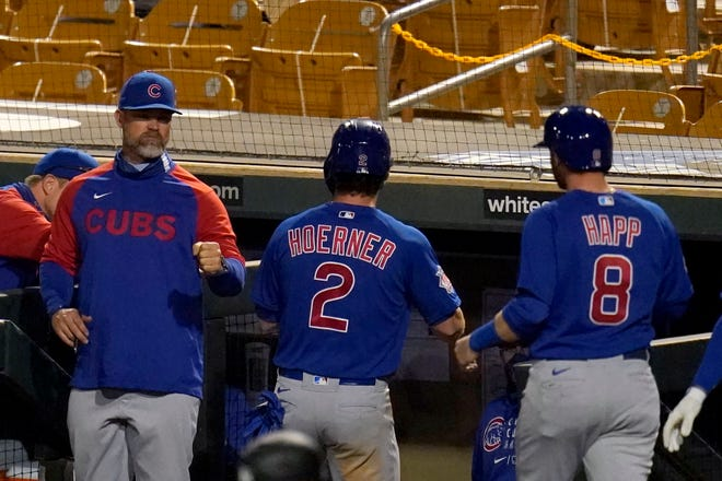 Chicago Cubs manager David Ross, left, congratulates Cubs' Nico Hoerner (2) and Ian Happ (8) after they both scored runs against the Los Angeles Dodgers during the third inning of a spring training baseball game Thursday, March 4, 2021, in Phoenix.