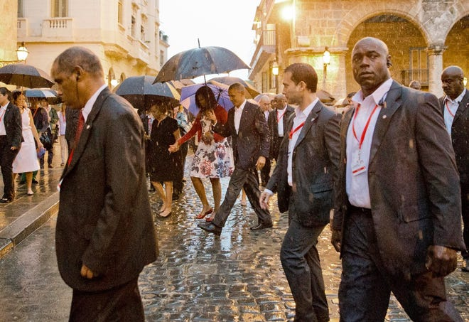 """In this Sunday, March 20, 2016 photo, President Barack Obama, center, walks in the rain with first lady Michelle Obama, who holds hands with her mother Marian Robinson during a walking tour of Old Havana, Cuba. Capping his remarkable visit to Cuba, Obama declared an end to the """"last remnant of the Cold War in the Americas"""" and openly urged the Cuban people to pursue a more democratic future for this island nation 90 miles from the Florida coast."""