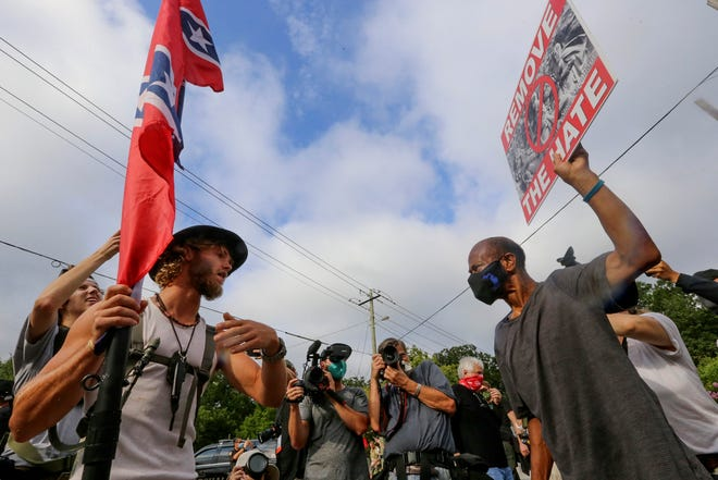 FILE - In this Aug. 15, 2020, file photo, protesters and counterprotesters face off in Stone Mountain Village, Ga. White supremacist propaganda reached alarming levels across the U.S. in 2020, according to a new report that the Anti-Defamation League shared with The Associated Press. (Jenni Girtman/Atlanta Journal-Constitution via AP, File)