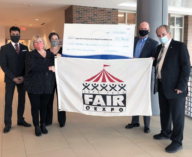 Cape Fear Fair and Expo President Debbie Carter and Fair Manager/Director Skip Watkins (front row) present a scholarship check to CFCC's Vice President for Advancement and the Arts Shane Fernando; Director of Philanthropy Logan Thompson; and President Jim Morton (back row).