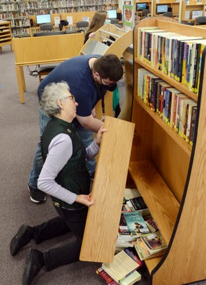 Gretchen Kolek, library assistant and Andrew Tingley, I. T. support specialist at Killingly Public Library put together a new bookcase Wednesday as the library received a $32,800 grant for new tables, chairs, bookcases and outdoor WiFi access. [John Shishmanian/ NorwichBulletin.com]