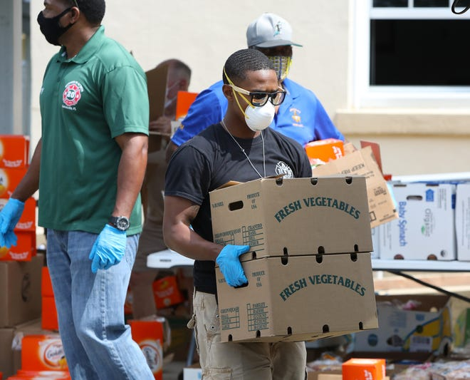 Devonte Simon, center, a firefighter with Gainesville Fire Rescue and a member of the group Brothers in Action, carries boxes of groceries to a vehicle during a drive-thru food distribution event in Waldo on May 13 in response to the COVID-19 pandemic.