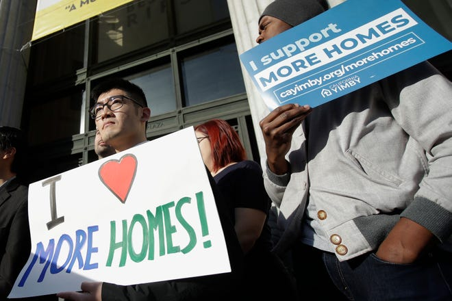 In this Jan. 7, 2020, photo, demonstrators hold up signs at a rally in Oakland, Calif., in support of efforts to override local zoning laws to allow multi-unit buildings in neighborhoods reserved for single-family homes.