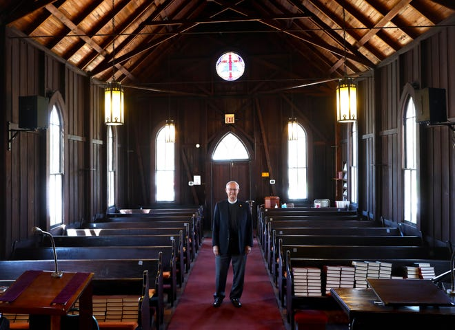 Rev. Lance Horne, pastor of St. Bartholomew's Episcopal Church, stands in the sanctuary, which is built of wood from fallen trees from the great storm of 1896, in High Springs. This year the church, which is built in the Carpenter's Gothic style made popular in the 1800s, is celebrating its 125th anniversary.