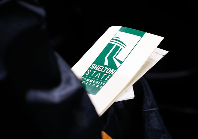 A graduate holds a program as Dr. Chuck Karr, the dean of the college of engineering, gives the commencement address in the gymnasium during graduation at Shelton State Community College on Friday, May 4, 2018. [Staff Photo/Erin Nelson]