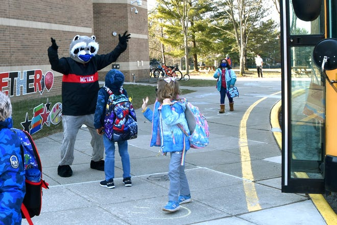 First-grader Muhammad Kourouma greets Rocky Raccoon, McVay Elementary School's mascot, as kindergartner Lily Fullroth waves while heading to the building from the school bus March 8.