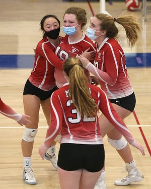 Milton's Katie Eckardt is embraced by Avery Liou and Sophia Manning after scoring a point during fourth set action of their match against Braintree at Braintree High on Tuesday, March 16, 2021.