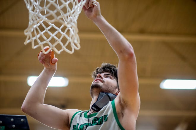 Pennfield senior Ryne Petersen (23) cuts a piece of the net on Tuesday, March 16, 2021 at Pennfield High School. Pennfield defeated Coldwater 44-41, winning the Interstate 8 Conference title.
