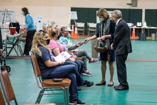 Ohio governor Mike DeWine and his wife Fran talk to residents as Fran passes out treats to people as they receive the coronavirus vaccine at OU-C Shoemaker Center on March 17, 2021.
