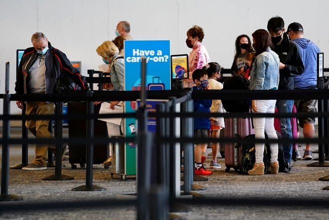 Passengers wait in the ticketing line on March 16, 2021, at the Cincinnati/Northern Kentucky International Airport in Hebron.