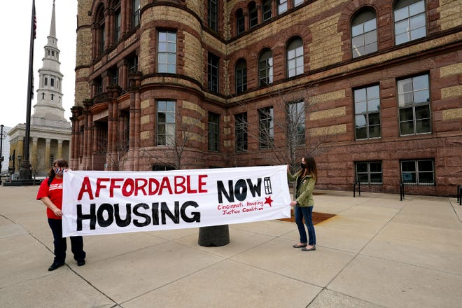 Susan Gregson, of Clifton, left, and Annabelle Arbogast, of College Hill, both of the Cincinnati Housing Justice Coalition, hold a banner in support of the affordable housing amendment, which would invest $50 million or more every year for affordable housing, Wednesday, March 17, 2021, outside front of Cincinnati City Hall.