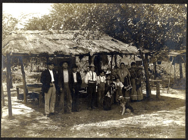 A Meskwaki group gathers beside a summer shelter in their settlement in Tama County around 1910.