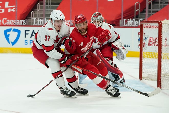 Sayap kanan Carolina Hurricanes Andrei Svechnikov (37) bersepatu roda dengan center Detroit Red Wings Luke Glendening (41) pada babak kedua pertandingan hoki NHL Selasa, 16 Maret 2021, di Detroit.