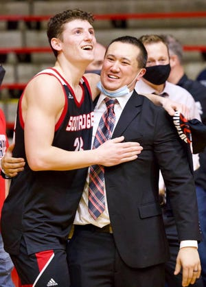 Southridge's Colson Montgomery (left) and coach Mark Rohrer celebrate the Raiders' first regional title since 1986 last Saturday.