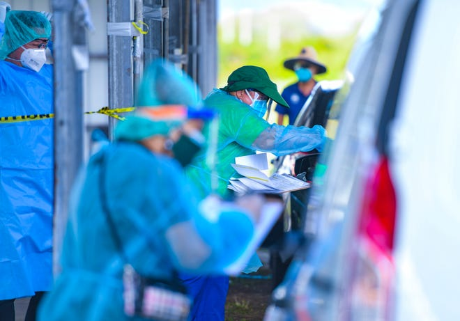 Department of Public Health and Social Services employees and other health care personnel conduct free drive-through COVID-19 testing on March 17 at the old carnival grounds in Tiyan.