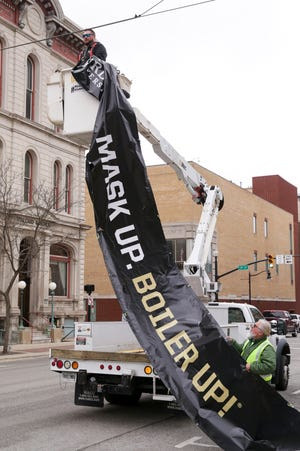 """Workers install a sign above Columbia Street reading """"Mask Up. Boiler Up."""" before Mackey Arena's first NCAA Men's Basketball Tournament games start, Wednesday, March 17, 2021 in Lafayette."""