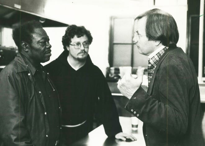 """Bill Moyers (right) of CBS talked with volunteer Eddie Griffin (left) and Father Steve Gliko at St. Benedict the Moor Catholic Church for CBS Reports: """"People Like Us."""" This photo was taken in 1982."""