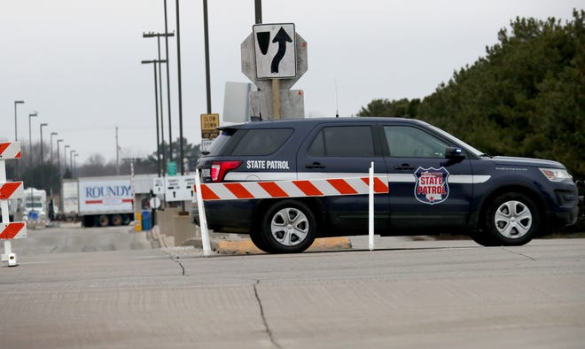 A Wisconsin State Patrol vehicle blocks an entrance to a Roundy's distribution center in Oconomowoc, Wisconsin, where two employees were killed Tuesday night.