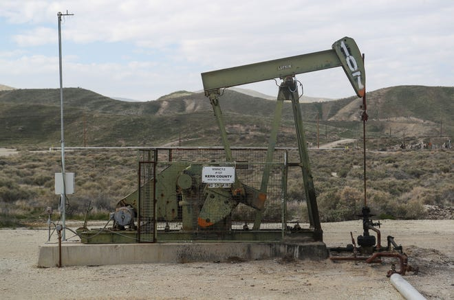 An oil derrick pumps near Maricopa in Kern County, California, February 21, 2020.
