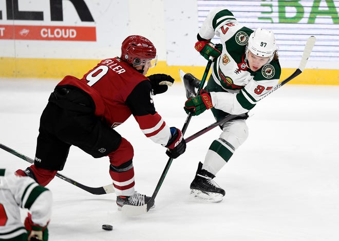 Minnesota Wild's Kirill Kaprizov (97), of Russia, passes away from Arizona Coyotes' Clayton Keller (9) during the first period of an NHL hockey game Tuesday, March 16, 2021, in St. Paul, Minn. (AP Photo/Hannah Foslien)