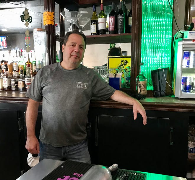 Port Huron Conner Street Pub owner Dino Tata stands behind the bar on March 16, 2021.