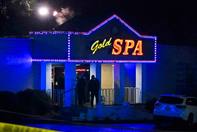 Law enforcement officials confer outside a massage parlor following a shooting on Tuesday, March 16, 2021, in Atlanta. Shootings at two massage parlors in Atlanta and one in the suburbs have left multiple people dead, many of them women of Asian descent, authorities said Tuesday. (AP Photo/Brynn Anderson)