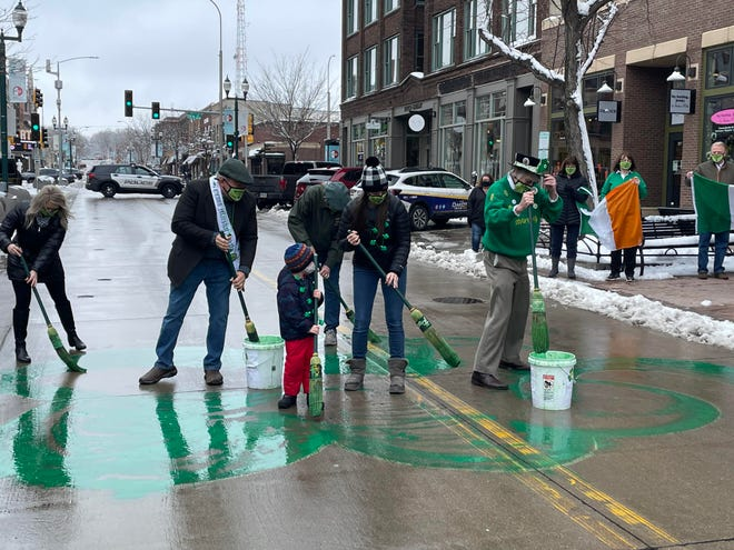 Volunteers paint a shamrock on Phillips Avenue, an annual Sioux Falls tradition.