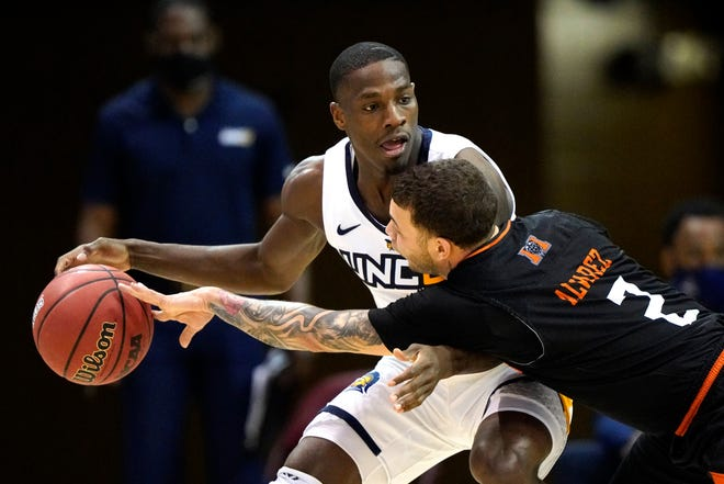 Mercer guard Neftali Alvarez (2) tries to steal the ball from UNC Greensboro guard Isaiah Miller (1) in the second half of an NCAA men's college basketball championship game for the Southern Conference tournament, Monday, March 8, 2021, in Asheville, N.C. (AP Photo/Kathy Kmonicek)