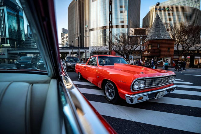 This picture taken on January 16, 2021 shows a 1964 Chevrolet El Camino Chevrolet (R) seen through the window of a 1959 Cadillac Coupe DeVille during a gathering of auto enthusiasts in Tokyo.