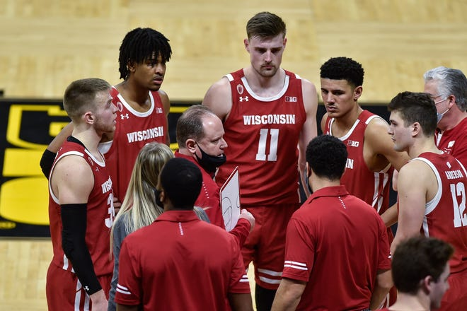 Badgers head coach Greg Gard talks with guard Trevor Anderson (12) and guard Brad Davison (left) and forward Micah Potter (11) late in the second half against the Hawkeyes at Carver-Hawkeye Arena.