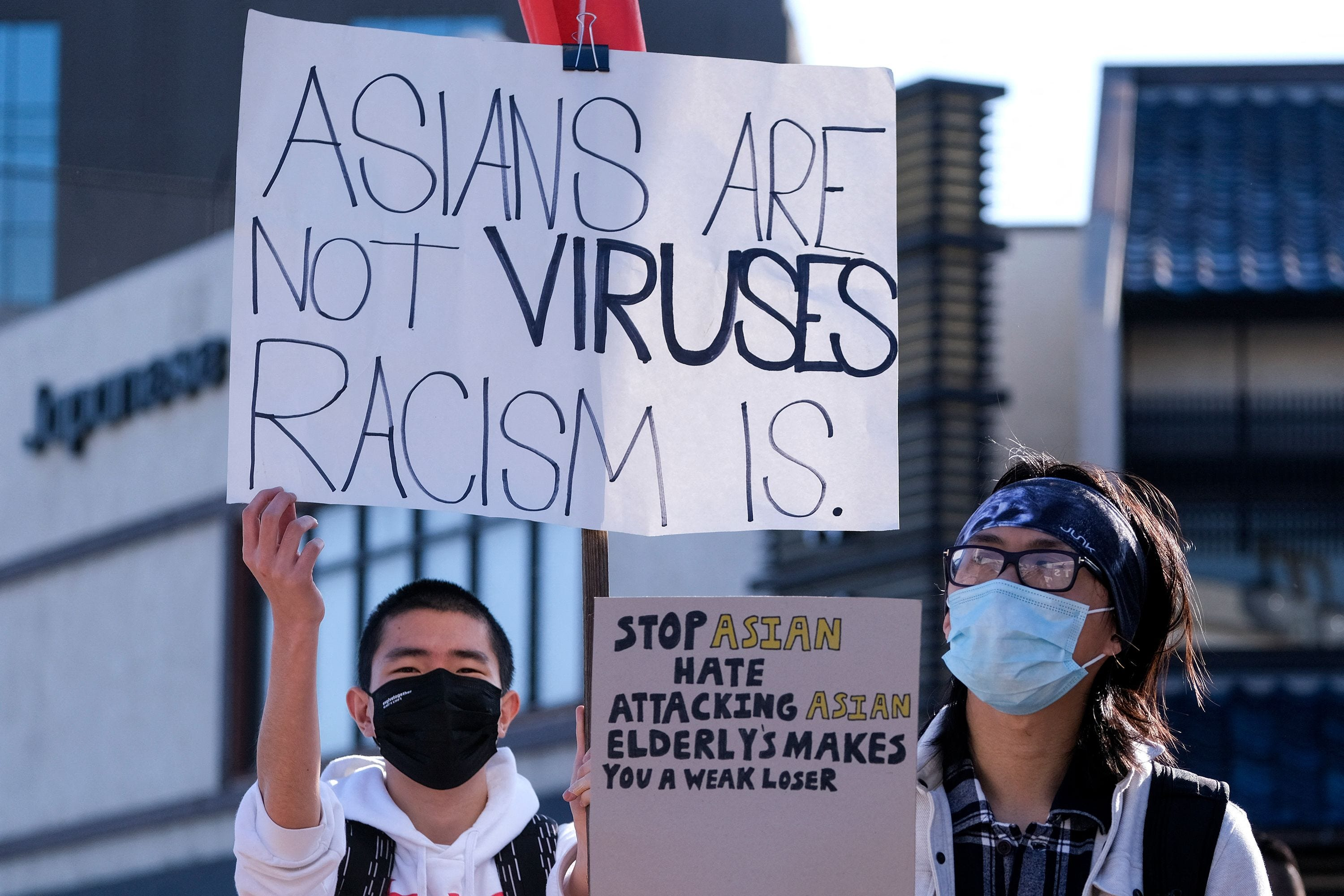 Two people hold up signs declaiming anti-Asian violence.