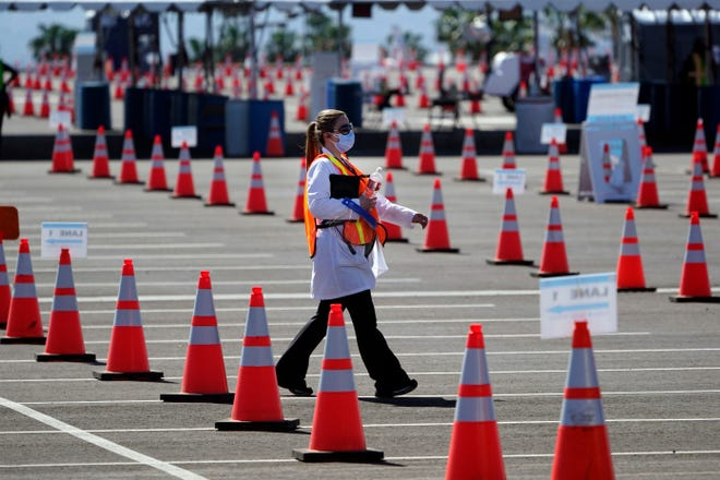 Sossie Bedrossian, head of nursing for the Los Angeles school district, walks in the parking lot of a COVID-19 vaccination site for district employees at SOFI Stadium Tuesday, March 2, 2021, in Inglewood, Calif. (AP Photo/Marcio Jose Sanchez)