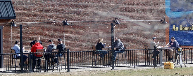 Customers eat at the outdoor eating area at Ohio Fire on East Main Street on Friday, March 12