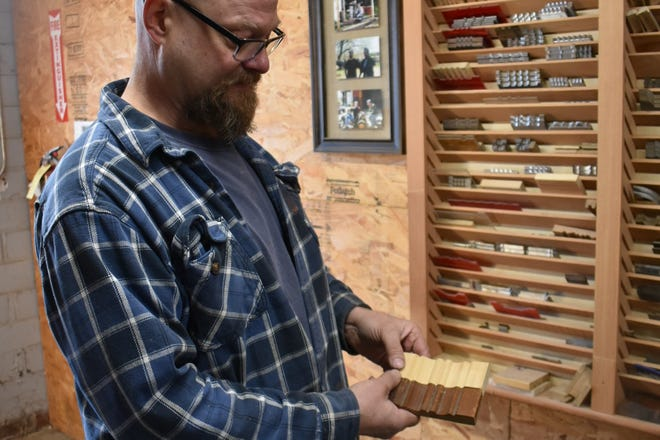 Luke Ulrich, owner of Great Planes Millwork, shows  a piece of original moulding and the copy he made of it. He custom grinds knives to match the details.