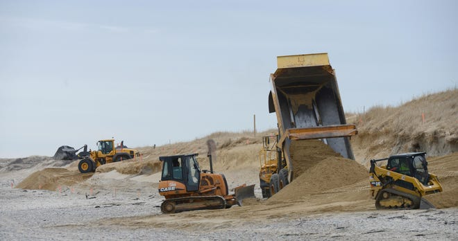 Sand is moved into place at Sandy Neck Beach as work continues to repair the dune fronting the main parking lot after erosion from two winter storms.