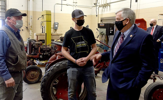 Gov. Mike Parson, right, visits with Mike Kilfoil, left, agricultural mechanics and welding technology instructor, and Hickman High School senior Thomas Wood on Thursday during the governor's tour of the Columbia Area Career Center. The governor toured various classes at the center as part of his advancement of workforce development in the state.