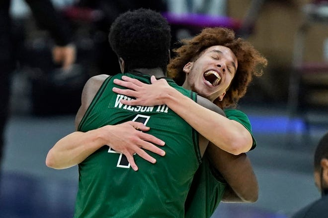 Jason Preston, right, celebrates with Ohio University teammate Dwight Wilson III after the Bobcats defeated Buffalo in the Mid-American Conference tournament final to qualify for the NCAA Tournament.