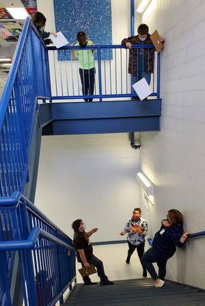 Students in the STEM Club do some research on aerodynamics in the stairwell.