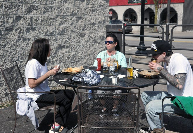 Tammy Hostetler and Autumn and Wolfgang Yeagley enjoy a relaxing lunch outside at Muddys restaurant in downtown Wooster.