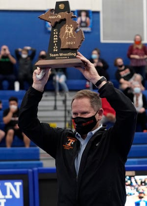 Tecumseh head coach George Lesko lifts up the Division 2 district championship after beating Adrian in the final at Adrian.