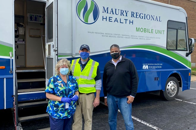 Maury Regional Health's Mobile Medical Unit's Lori Bergland, RN, left, and Director Patrick Harlan, center, pose with Carmack Boulevard Church of Christ Pastor Demetrius Nelson as the curch hosted the unite for a day of COVID-19 vaccine distributions in Columbia, Tenn., on Tuesday, March 16, 2021.
