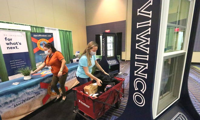 Crystal Hanks (center), owner of Abaco Windows, sets up the company's display for the 32nd Annual Spring Home Show at the Ocean Center with help from sales manager Jennifer Wiggins.  Presented by The Daytona Beach News-Journal, the free 3-day event opens on Friday in Daytona Beach.