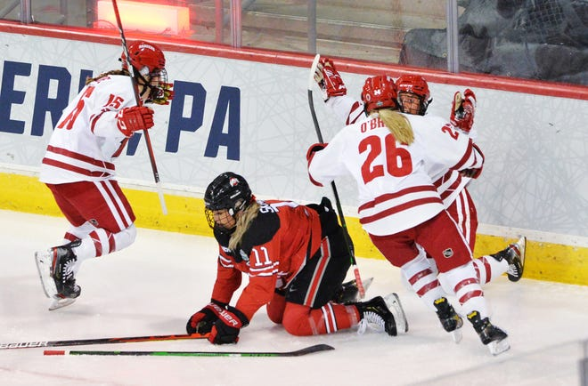 Ohio State's Tatum Skaggs (11) drops to the ice while Wisconsin's Caitliin Schneider (15) and Casey O'Brien (26) celebrate a goal by Makenna Webster just 79 seconds into the game to give the Badgers a 1-0 lead.