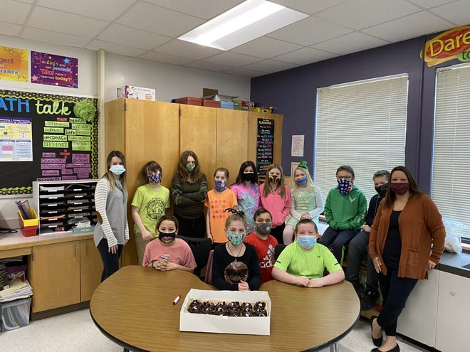 """Members of Barbara Macri's fifth grade class at Herkimer Elementary School prepare to sample the winning entry in their persuasive writing contest. Alaina Hutchinson designed and described the """"Chocolate Fudge Delight Adventure,"""" which is currently being made and offered at the Cakery Café LLC in Dolgeville."""