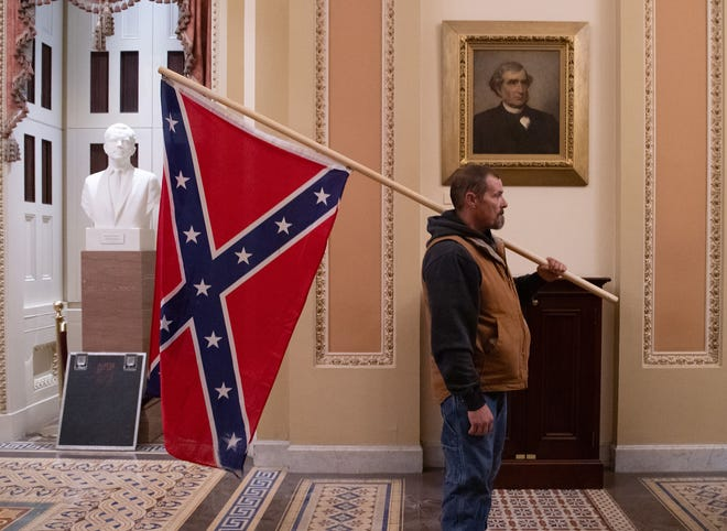 A supporter of President Donald Trump holds a Confederate flag outside the Senate Chamber during a rampage in the U.S. Capitol in Washington, D.C., on Jan. 6, 2021.