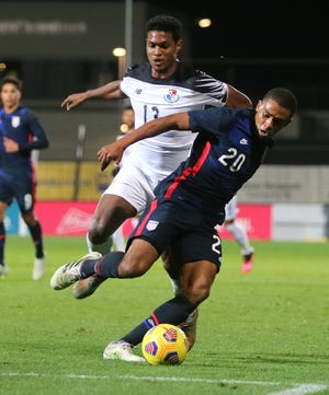 United States' Reggie Cannon, right, and Panama's Oscar Linton battle for the ball during the international friendly soccer match between the USA and Panama at the SC Wiener Neustadt stadium in Wiener Neustadt, Austria, Monday, Nov. 16, 2020. (AP Photo/Ronald Zak)