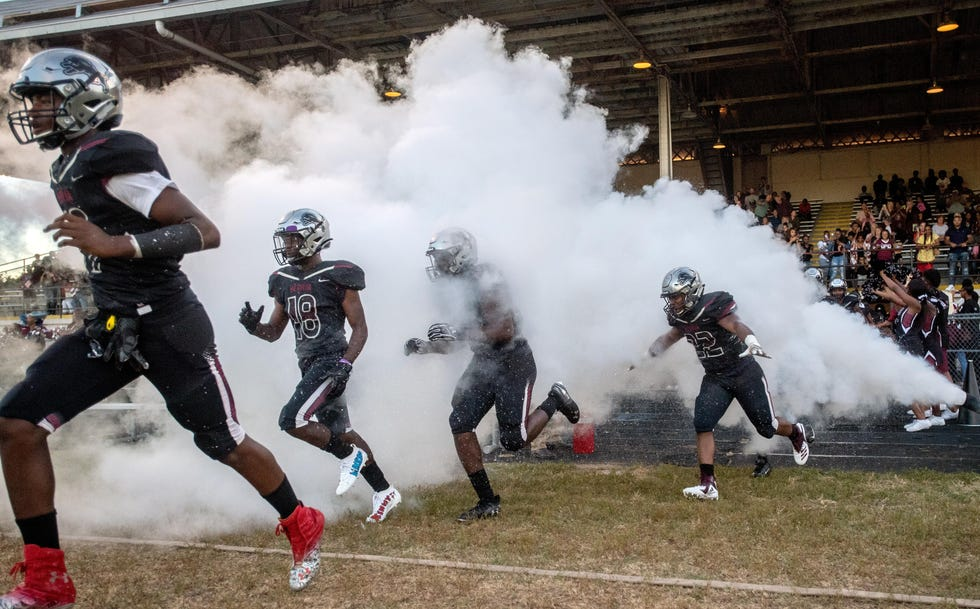 The Peoria High football team emerges from the locker room before a 2019 high school football game at Peoria Stadium.