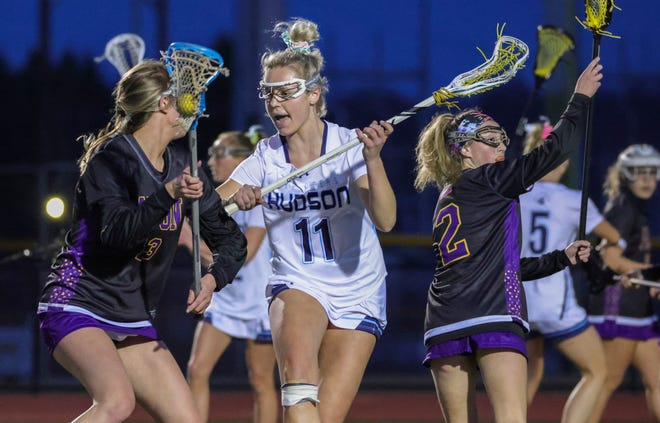 Hudson's Kate Orazen (center) defends as Hudson girls lacrosse takes on Avon in a scrimmage on Wednesday.
