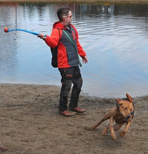 Stephen Archer gets set to throw the ball as Elvis, a Redbone Coonhound owned by Todd Butchko starts to run for the ball at Bow Wow Beach Dog Park on Tuesday March 16, in Stow. Archer was there with his dog Nyx, a Border Collie mix. [Mike Cardew/Akron Beacon Journal]